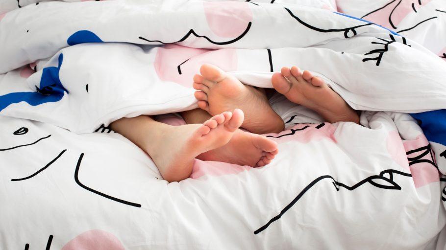 Zwei Füße unter der Bettdecke