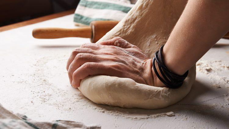 Hände kneten Teig auf bemehltem Tisch