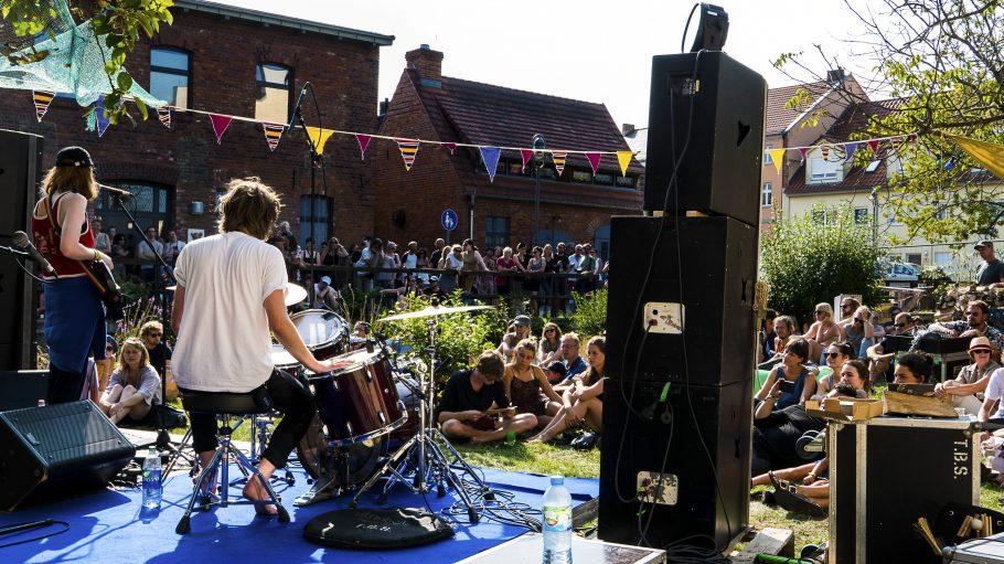 Ein Mann spielt Schlagzeug auf einer Bühne.