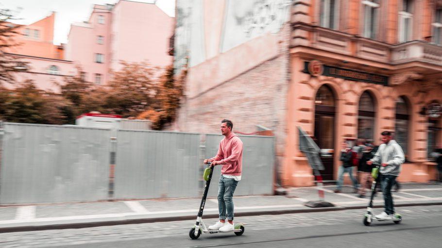 Ein Mann fährt auf einem E-Scooter die Straße entlang.