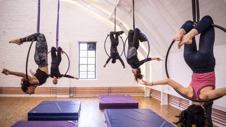 Fünf Frauen hängen kopfüber von den Aerial Hoop Ringen.