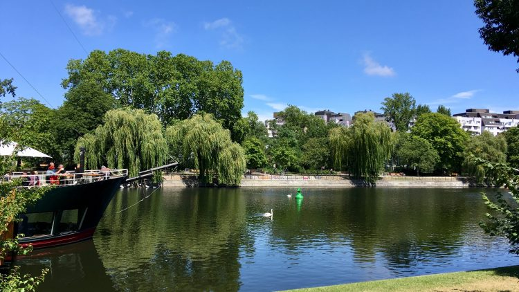 Landwehrkanal mit Bäumen am Ufer, Schwänen und einem Restaurantschiff