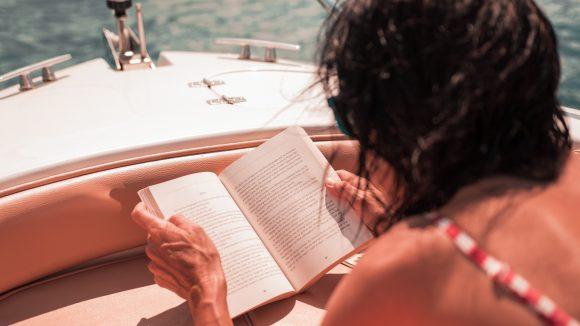 Frau liegt auf einem Boot und liest...