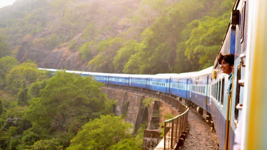 Zug fährt über eine Brücke, Frau streckt den Kopf raus.