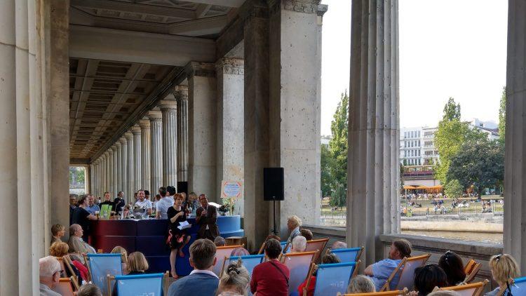 Menschen sitzen auf Liegestühlen in Säulengang und hören Mann und Frau zu, die an Bar lehnen