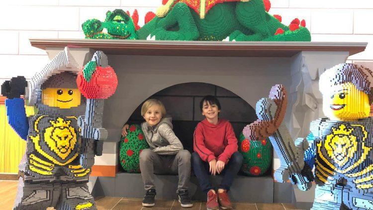 Kinder sitzen auf Kamin vor Legorittern in Menschengröße.
