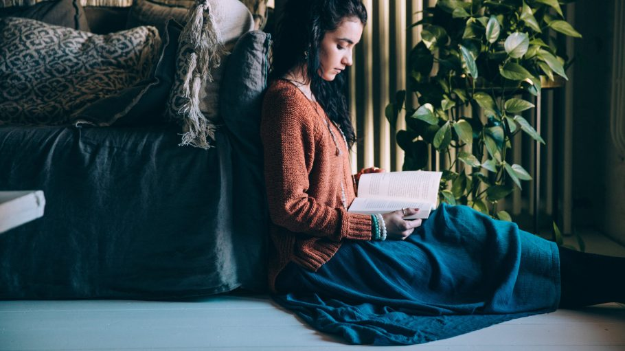 Eine lesende Frau sitzt im Wohnzimmer.