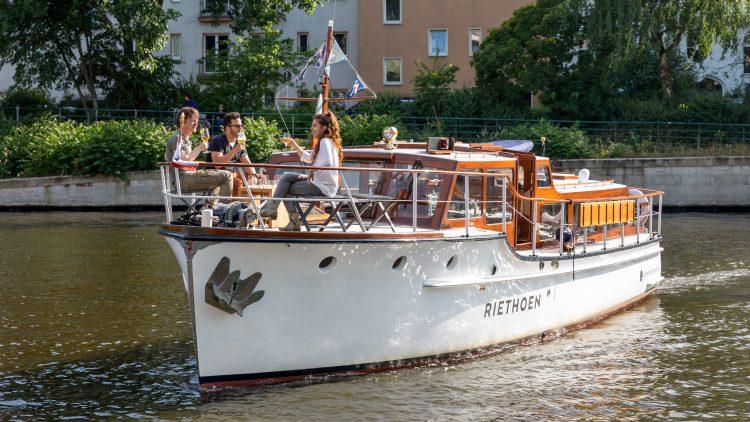altes Motorboot auf dem Wasser mit drei Passagieren