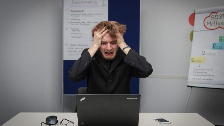 Mann rauft sich die Haare vor dem Laptop