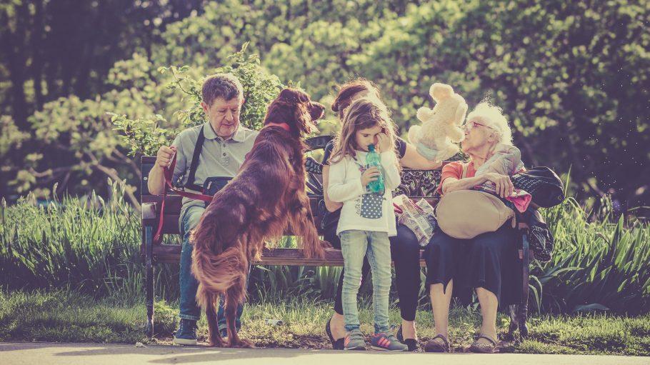 Eine Gruppe mit Kindern, Hund und Altehn sitzt zusammen auf einer Bank im Sonnenschein.