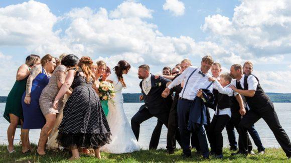 Hochzeitsgesellschaft vor einem See auf einer grünen Wiese.