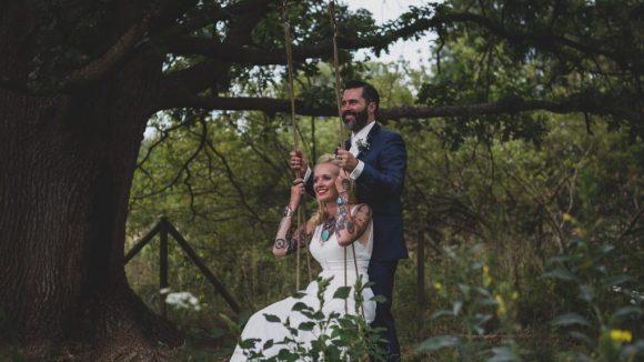 Braut im weißen Kleid sitzt auf einer Baumschaukel und hinter ihr steht der Bräutigam im Anzug.