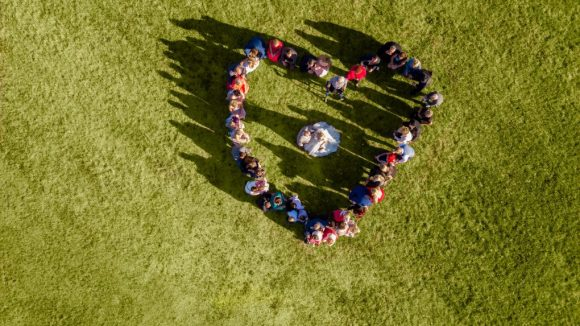 Eine Menschenmasse, die in Herzform auf einer Wiese steht und von einer Drohne fotografiert wurde.