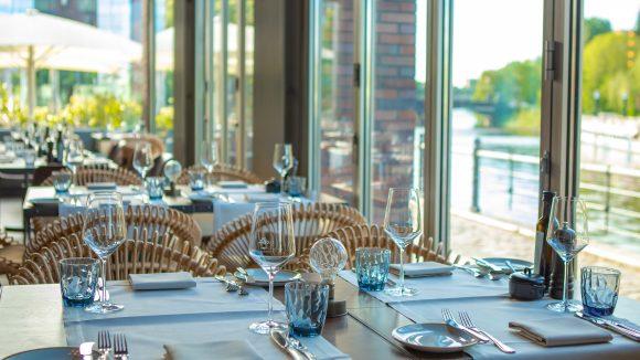 Gedeckter Tisch mit Glasfront und Blick aufs Wasser