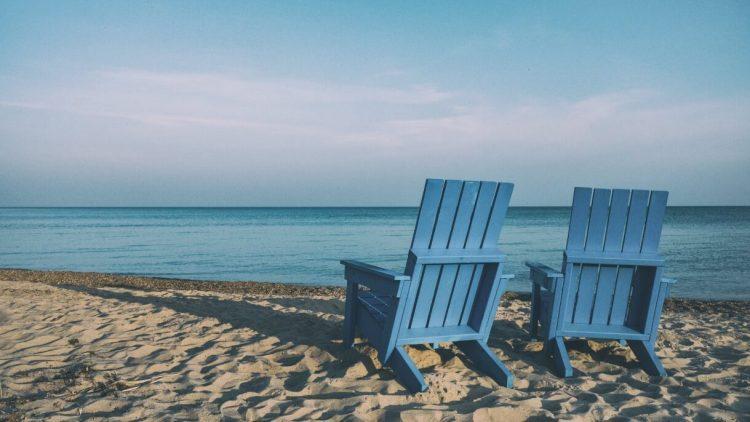 Blaue Holzstühle am Strand mit Blick auf das Meer und blauen Himmel