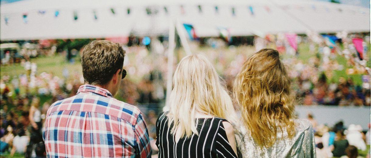 Zwei Frauen und ein Mann stehen auf einer Wiese und blicken Richtung Festzelt von Partyzelte Berlin.