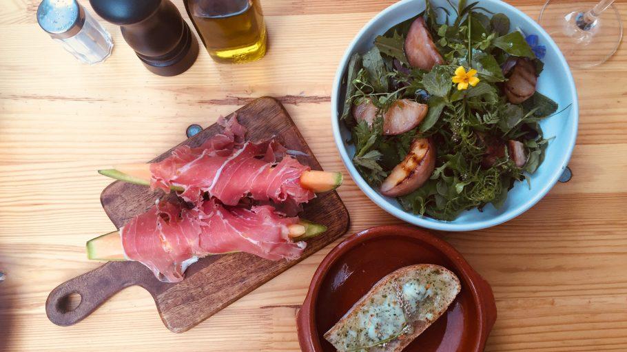 Ein Holztisch mit Tellern voller Melone mit Schinken, Wildkräutersalat und Brot mit Kräuter-Schweinefett-Aufstrich.