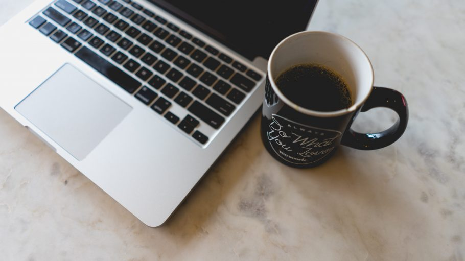 Nahaufnahme von Macbook und Kaffeetasse