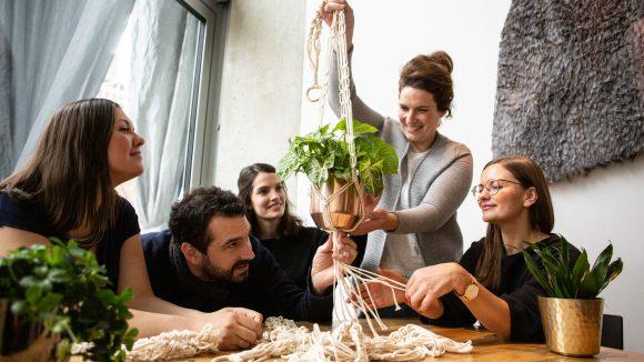 Menschen am Tisch, Frau in der Mitte hält Pflanze in Blumenampel