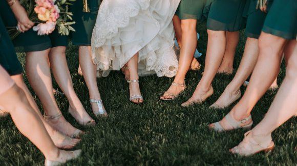 Braut und Brautjungfern stehen auf dem Rasen mit Schuhen