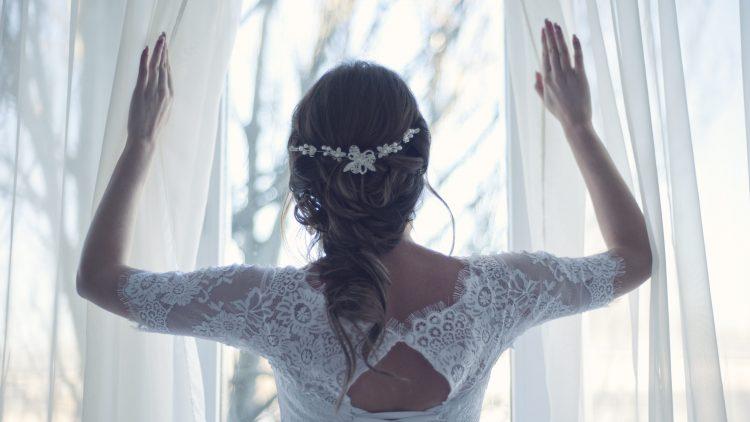 Eine Braut von hinten, die Vorhänge beiseite schiebt.