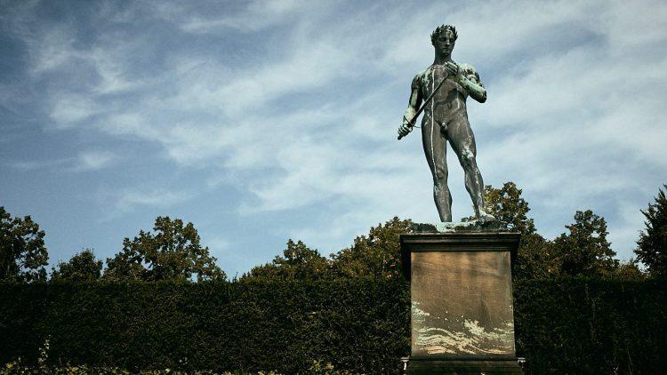 Steinstatue, männlich mit Schwert in der Hand und Siegerkranz steht in Park Sanssouci