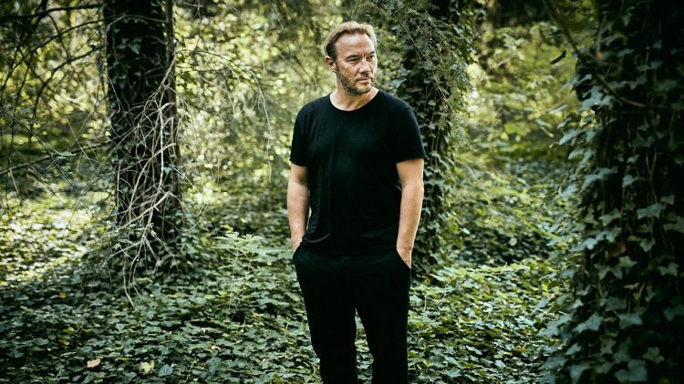 Thomas Arnold steht inmitten von Efeu, hinter ihm Bäume