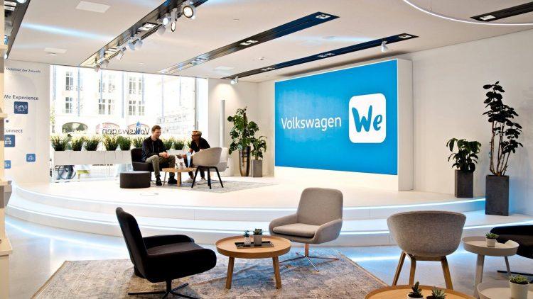 Großer Büroraum. In der hinten linken Ecke sitzen zwei Männer auf Stühlen und unterhalten sich.