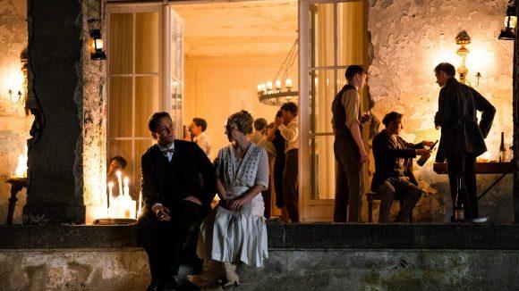 August Diehl als Walter Gropius und Anna Maria Mühe als Dörte Helm auf einer Terrasse am Abend.