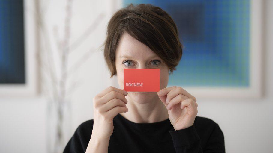 """Frau mit """"Rocken""""-Karte in den Händen vor ihrem Gesicht"""