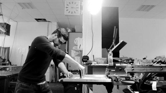 Mann mit schwarzem Pullover und Brille arbeitet in einer Siebdruckwerkstatt an einer Maschine