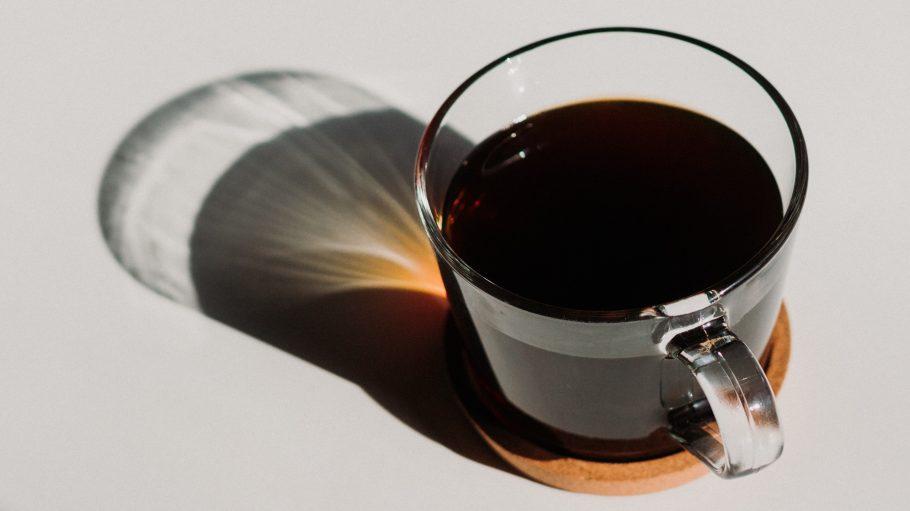 Schwarzer Kaffee auf Tisch in Sonne
