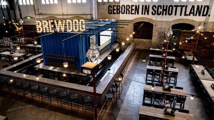 Großes Brauerei-Restaurant mit Bar um einen Container, Tische und Stühle in Industriehalle