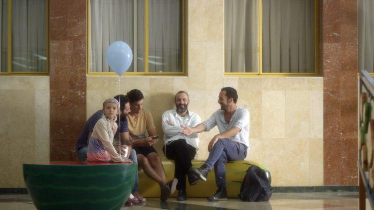 Filmstill mit vier dunkelhaarigen Männern, zwei mit Bart, die auf einem Bananen-Sitzmöbel sitzen, neben ihnen ein Kind mit Mütze und Luftballon.