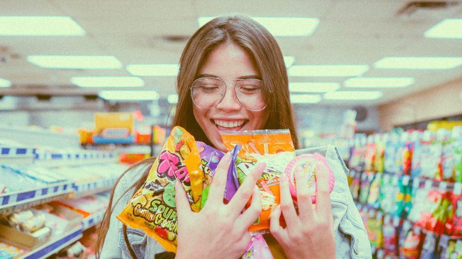 Mädchen im Laden mit Süßigkeitenpackungen im Arm.