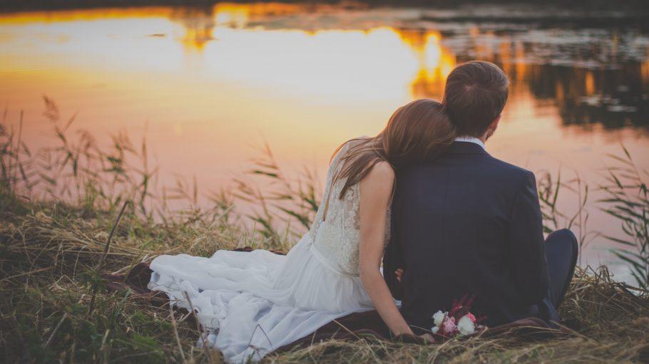 Brautpaar sitzt am Ufer eines Sees bei Sonnenuntergang im Gras.