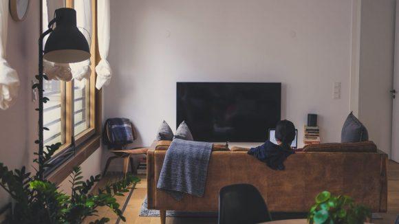 Person sitzt auf dem Sofa im Wohnzimmer einer WG