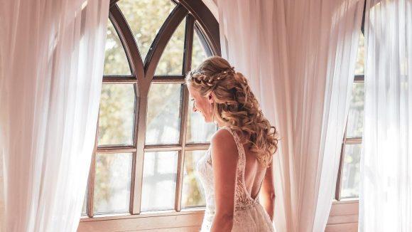 Braut steht am Fenster und sieht hinaus.