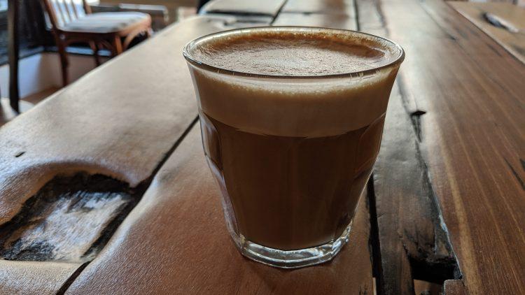 Ein Kaffee auf einem Holztisch.