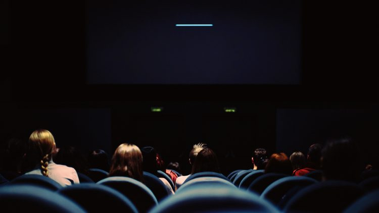 Schwarze Kinoleinwand mit weißem Streifen, blaue Kinosessel, Hinterköpfe von rund zehn Kinobesuchern