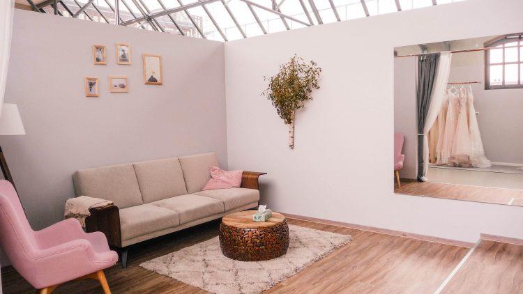 Sessel, rose Couch unter Bilderrahmen, Teppich und runter Holztisch mit Taschentüchern im Anprobezimmer von Vanity Bridal