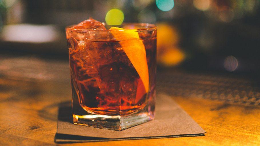 Glas mit Longdrink, braun, Eiswürfel, Zitrone, steht auf Pappe auf Tresen