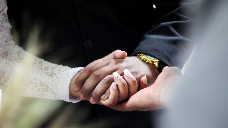 Ein Brautpaar hält sich bei den Händen.