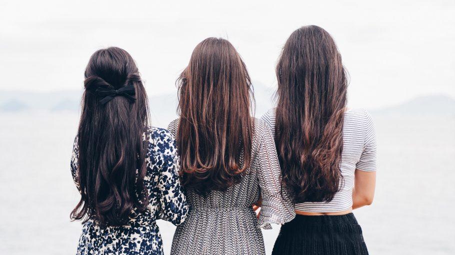 Drei dunkelhaarige Frauen mit Langhaarfrisuren von hinten.