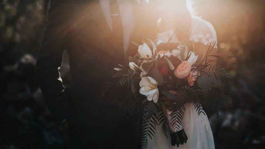 Brautpaar gegen das Licht in der Abendsonne fotografiert, Brautstrauß in weiß, rosa und rot.