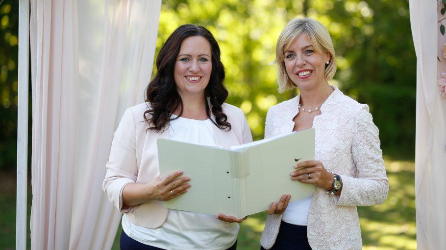 Zwei Frauen, eine mit dunklen Haaren über die Schulter, die andere blonde nackenlange Haare, halten weiße Mappe in der Hand, stehen unter Vorhang