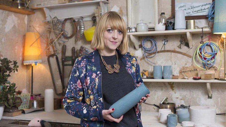 Frau Anna Diekmann, mit schulterlangen blonden Haaren und Blümchenjacke hält graublaue Vase in der Hand, im Hintergrund ein Atelier