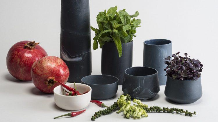 Graue Vase und mehrere kleinere Gefäße, zwei mit Kräutern drin, stehen auf Tisch