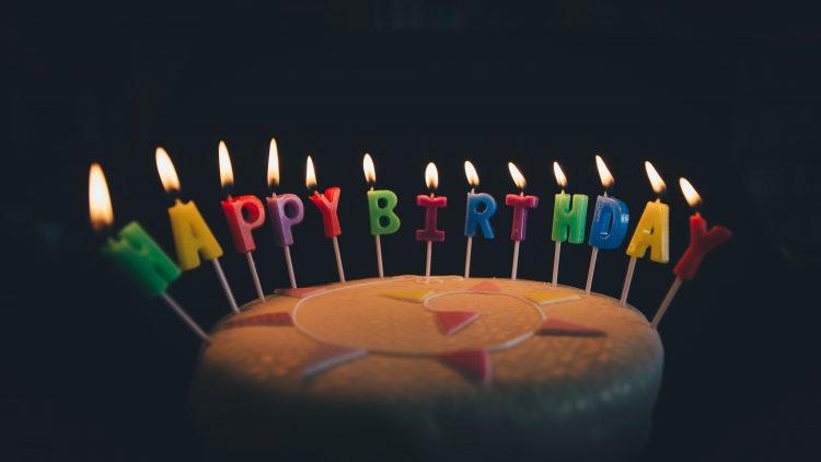Ein Geburtstagskuchen mit brennenden Happy Birthday Buchstaben.