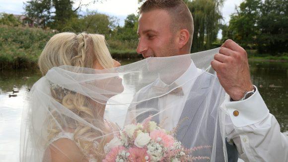Braut und Bräutigam lächeln sich an. Bräutigam hält Schleier halb hoch